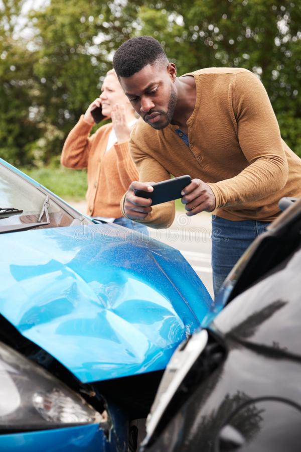 Male Motorist Involved In Car Accident Taking Picture Of Damage For Insurance Claim royalty free stock image