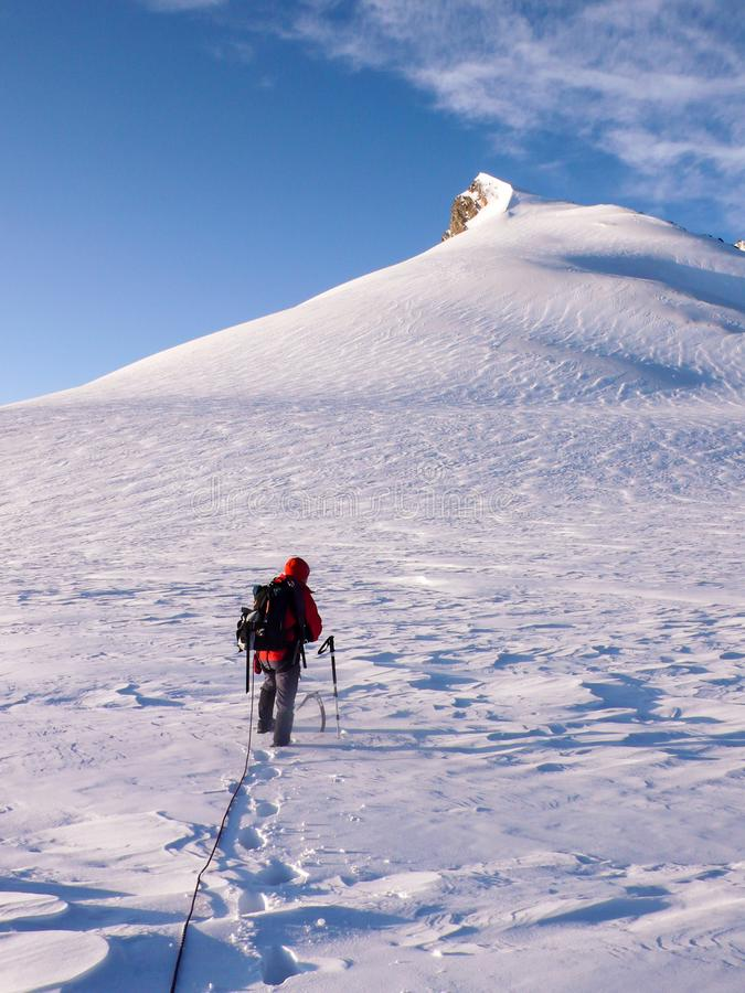 Male mountain climber heads towards a high alpine summit over a glacier with fresh snow royalty free stock photos
