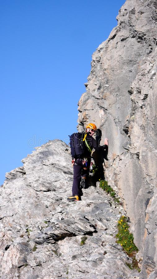 Male mountain climber at the start of a long climbing route under a clear blue sky. A male mountain climber at the start of a long climbing route under a clear royalty free stock photos
