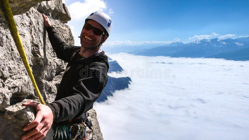 Male mountain guide smiling on a steep vertical rock climb in gorgeous surroundings high above a sea of clouds in the valley below royalty free stock photo