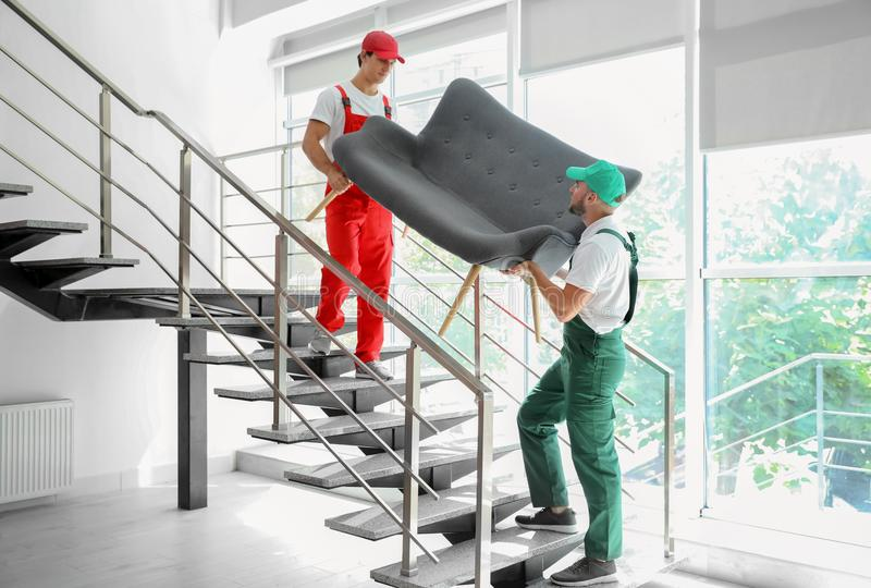 Male movers carrying sofa stock image