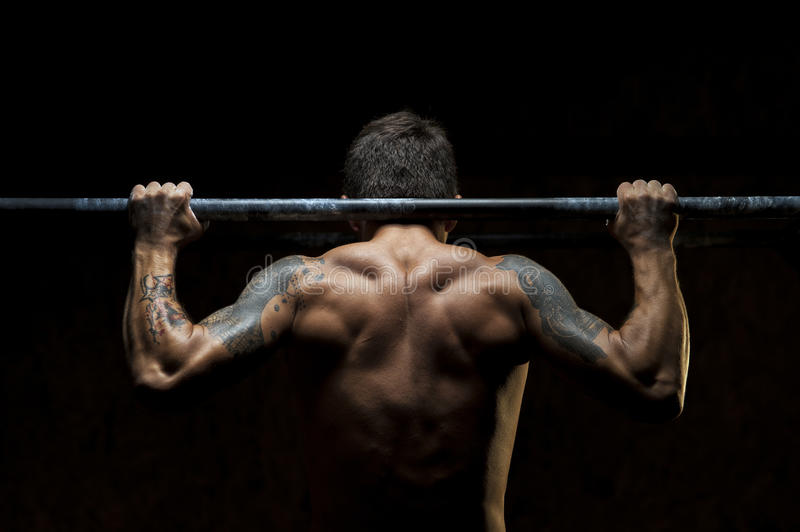 Male muscular athlete doing pull up exercise. Back view of male muscular athlete doing pull up exercise on horizontal bar. Fitness, gymnastics workout in gym royalty free stock photography