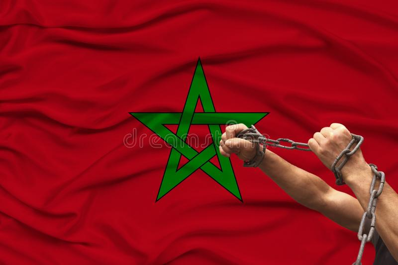 Male muscular hands of a prisoner in iron chains against the background of the national flag of the state of Morocco, the concept royalty free stock photo