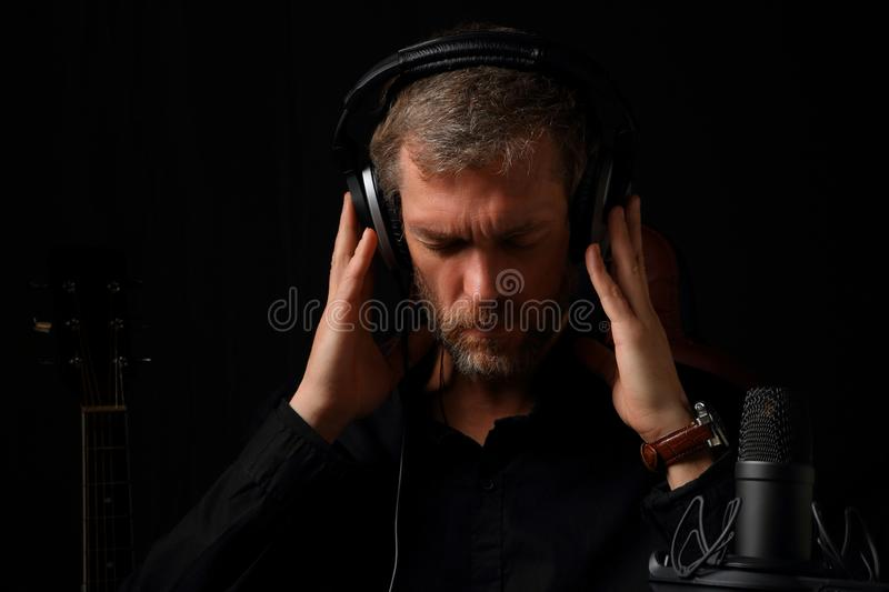 A man in headphones listening to music on a dark background stock photos