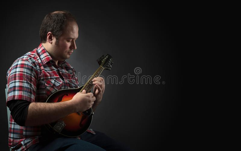 Male musician sits and plays a lute stock photography