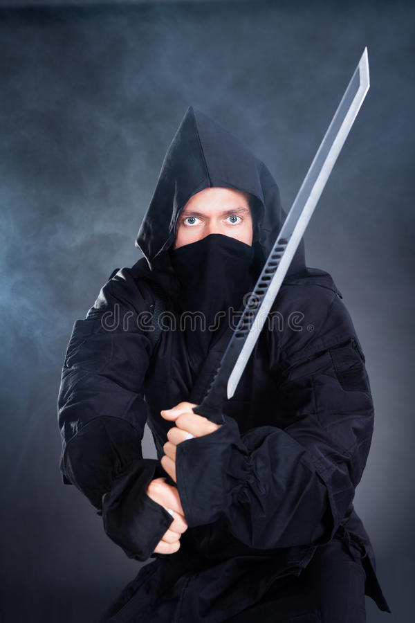 Male Ninja In Black Costume Holding Sword stock photos