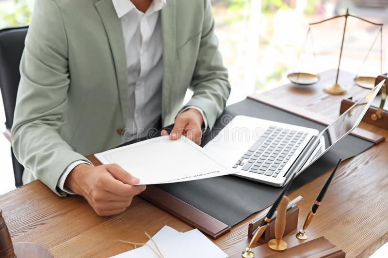 Male notary with documents and laptop at table in office. Closeup stock image