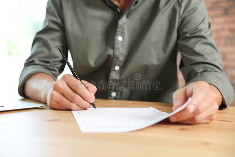 Male notary signing document at table. In office, closeup stock photography