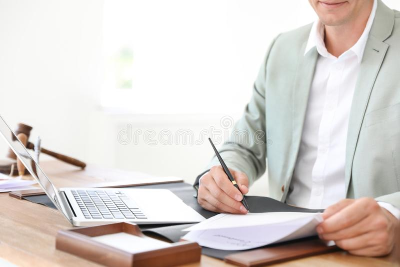 Male notary signing document at table in office. Closeup stock photography