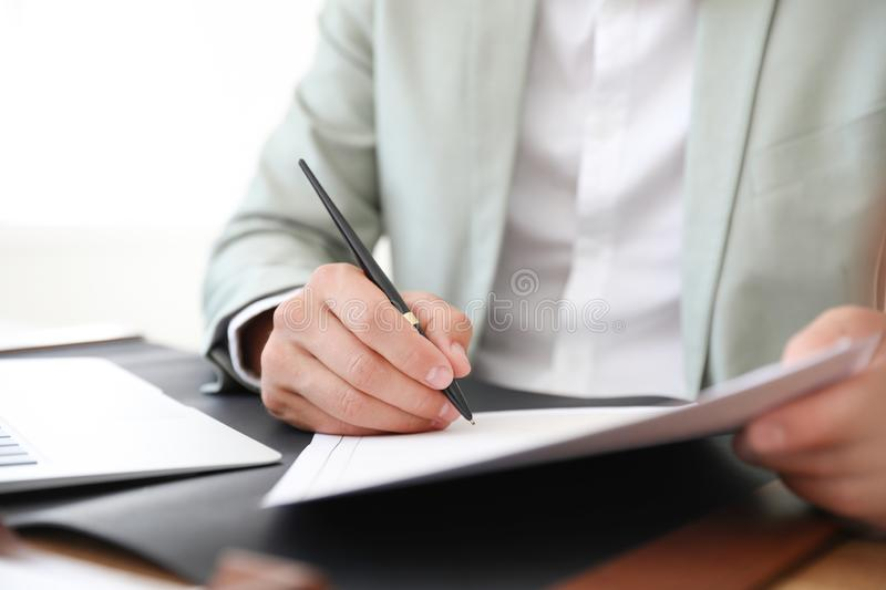 Male notary signing document at table in office. Closeup stock photos