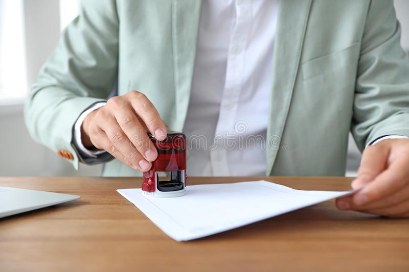 Male notary stamping document at table in office. Closeup royalty free stock image