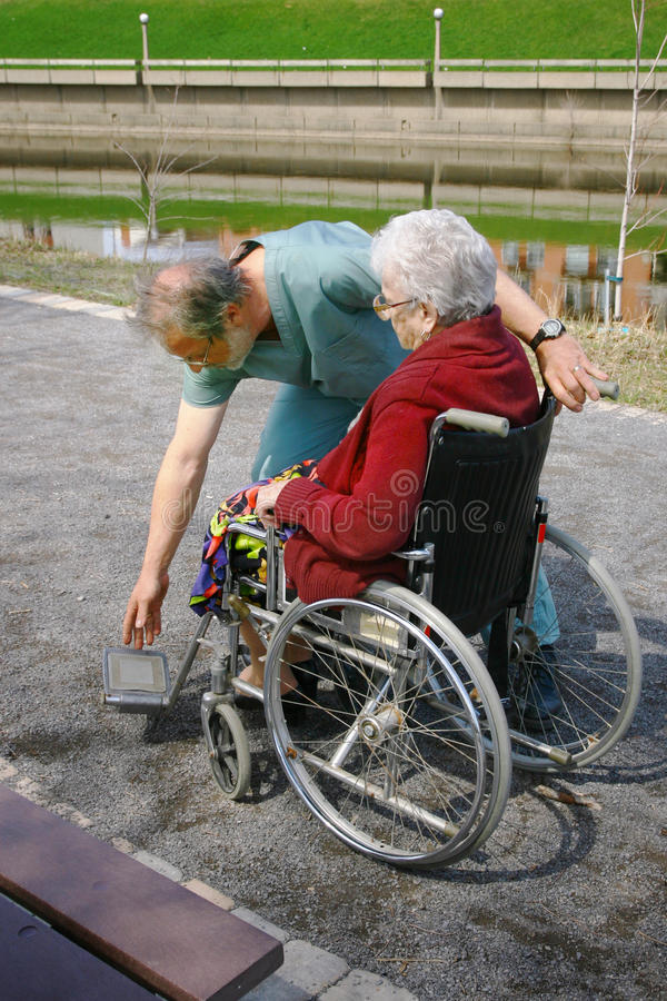 Male nurse. Shown assisting a woman in a wheelchair royalty free stock photo