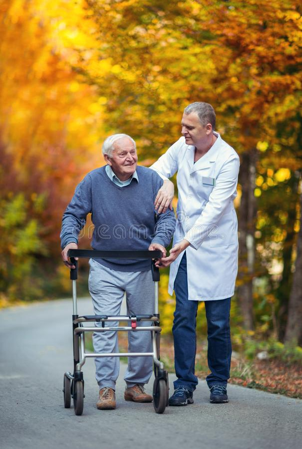 Male nurse assisting senior patient with walker in park stock images