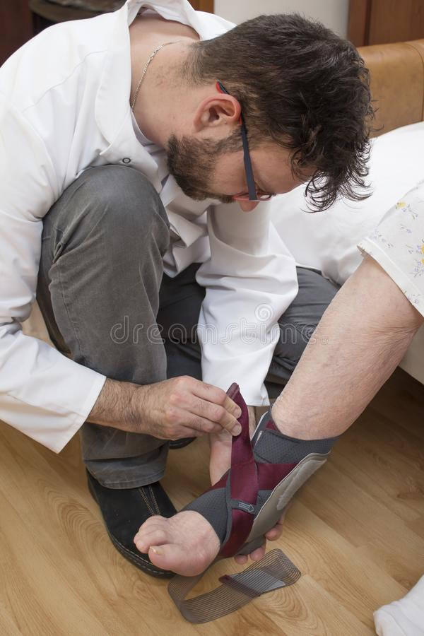 Male nurse assumes an ankle stabilizer on the leg of an old woman. stock photos