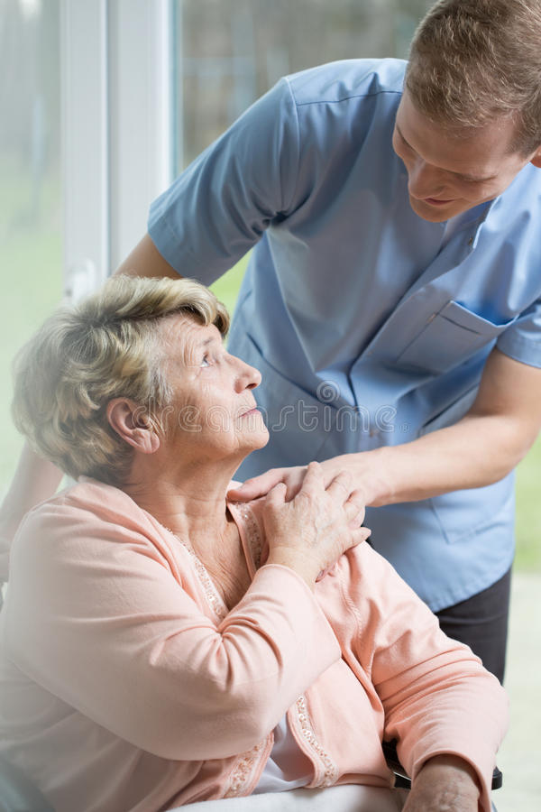 Male nurse caring about ill woman. Male nurse caring about ill senior woman royalty free stock images