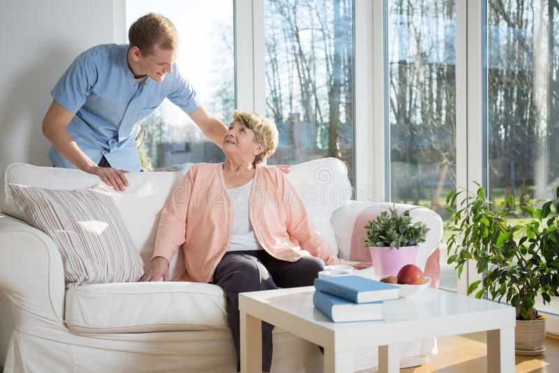 Male nurse caring about patient. At home stock images