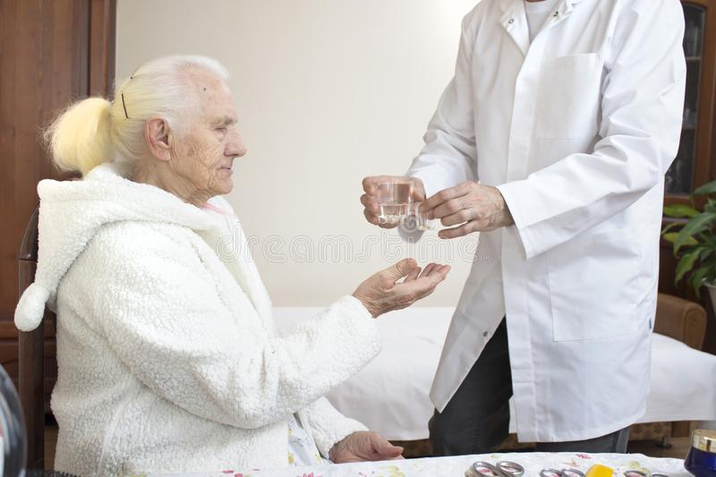 Male nurse supervises taking medicine by an old woman. royalty free stock photography