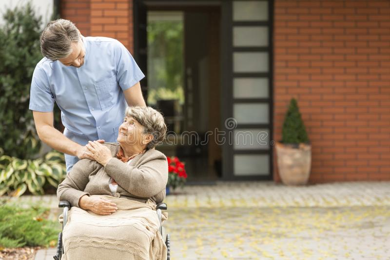 Male helping happy elderly woman in the wheelchair in front of house stock image