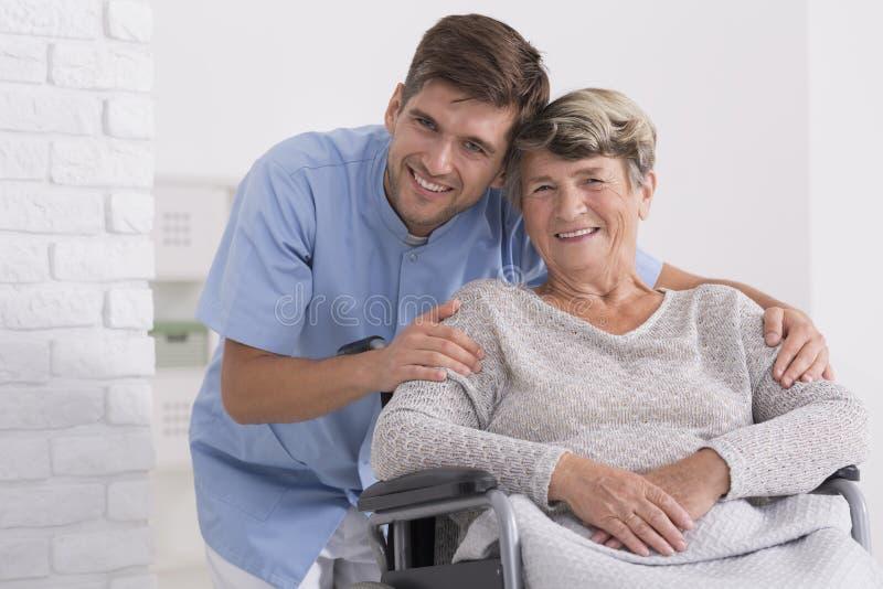 Male nurse hugging his senior woman patient. Male nurse hugging his senior women patient sitting on a wheelchair stock photos