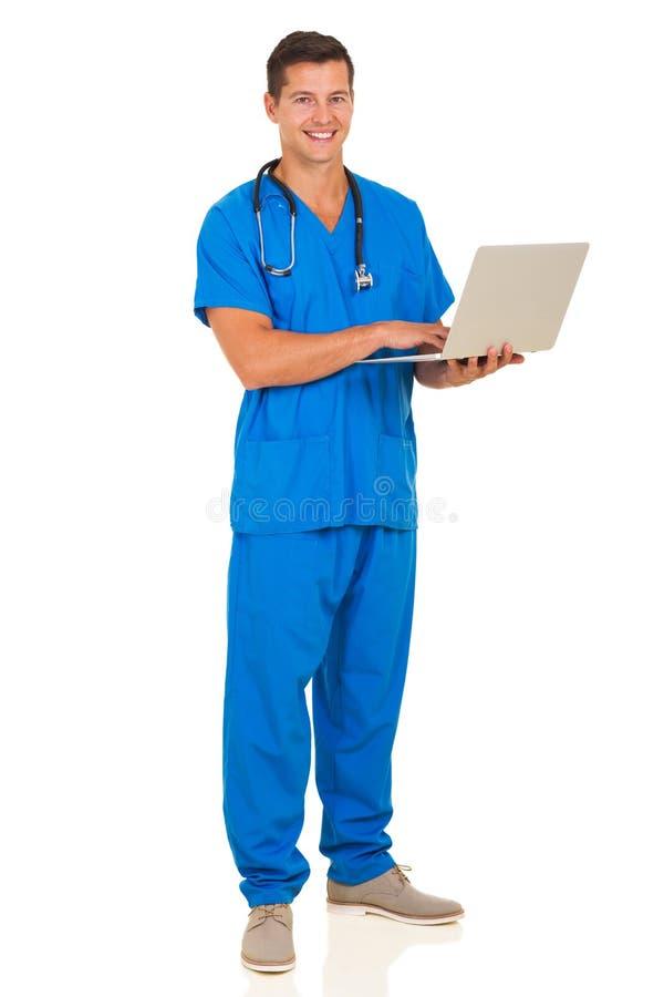 Male nurse laptop computer. Full length portrait of male nurse using laptop computer royalty free stock photography