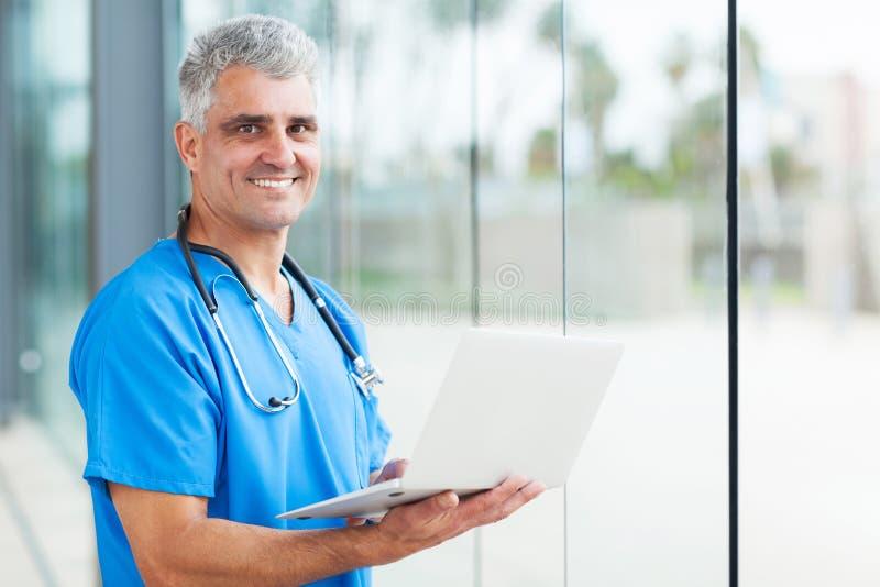 Male nurse laptop. Handsome senior male nurse using laptop stock images