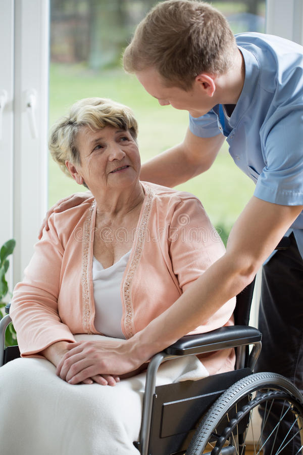 Male nurse and older woman. Male nurse and older women on wheelchair royalty free stock photo
