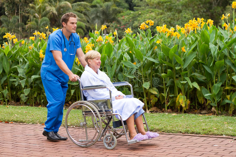 Male nurse and patient. Young male nurse pushing senior patient on wheelchair outdoors royalty free stock photos