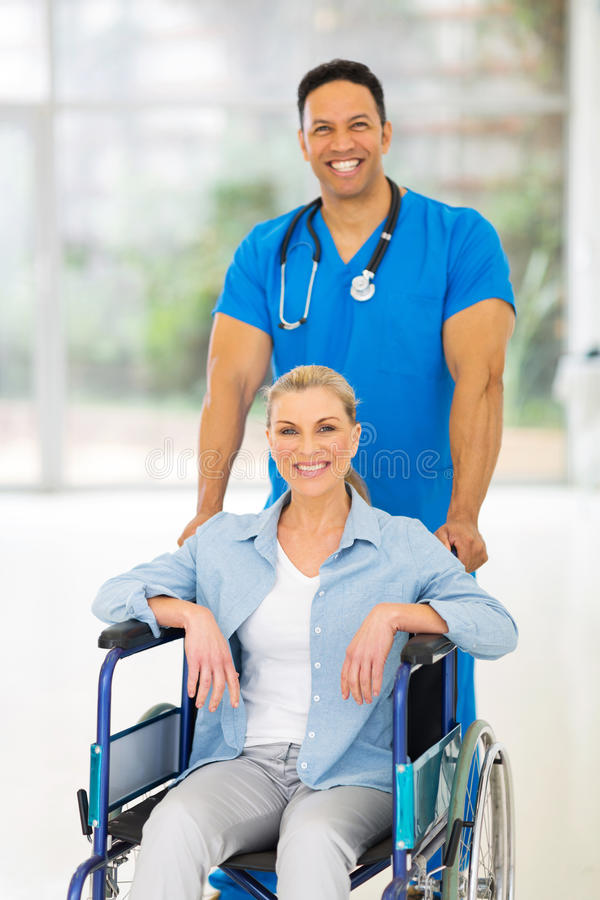 Male nurse patient. Handsome medical male nurse taking care of senior patient in wheelchair stock photo