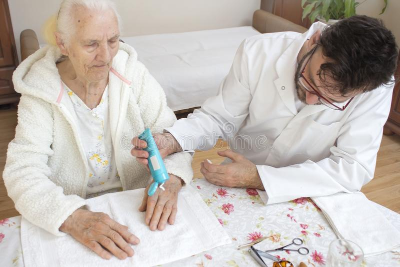 Male nurse puts the cream on the old woman`s hand. Cosmetic treatment and nursing. royalty free stock photos