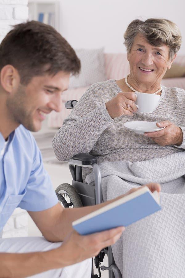 Male nurse reading a book to senior. Smiled male nurse reading a book to senior women with a cup of tea royalty free stock photography