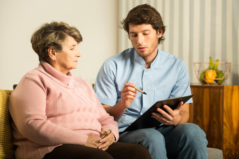 Male nurse in rest home. Male nurse working in rest home - horizontal view stock photos