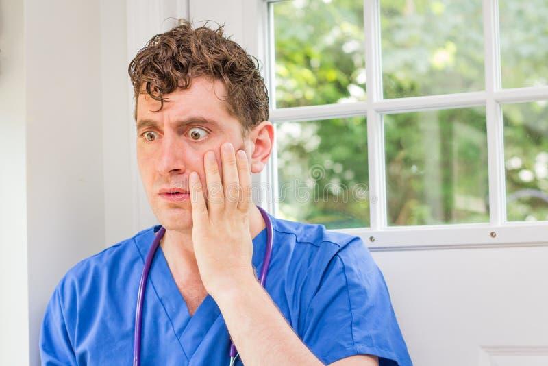 Male Nurse Stethoscope. Male nurse in scrubs with stethoscope makes huge mistake stock image