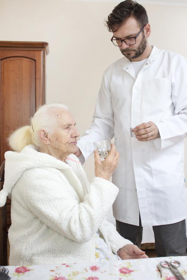 Male nurse supervises taking medicine by an old woman. stock image