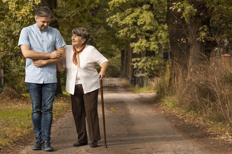 Male nurse supporting happy woman with walking stick in the forest stock photography