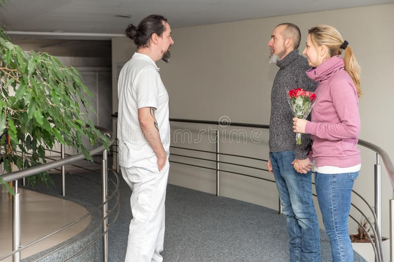 Male nurse with two visitors in a corridor royalty free stock photography