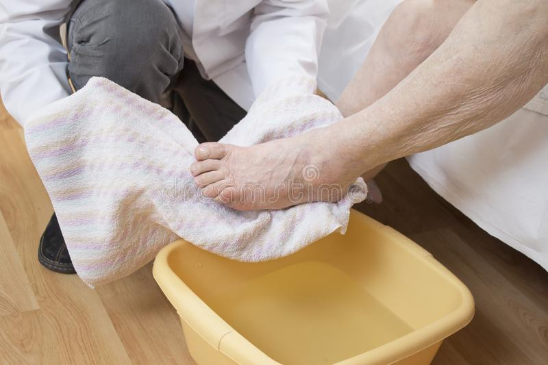 Male nurse wipes the feet of an old woman by a towel. stock image