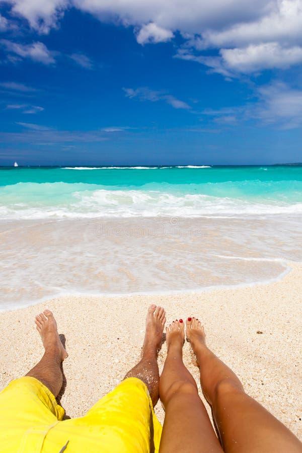 Male och kvinnligt lägger benen på ryggen på tropisk strand royaltyfria foton