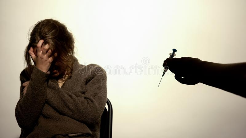 Male offering drug syringe to depressed young woman, psychological pressure royalty free stock photos