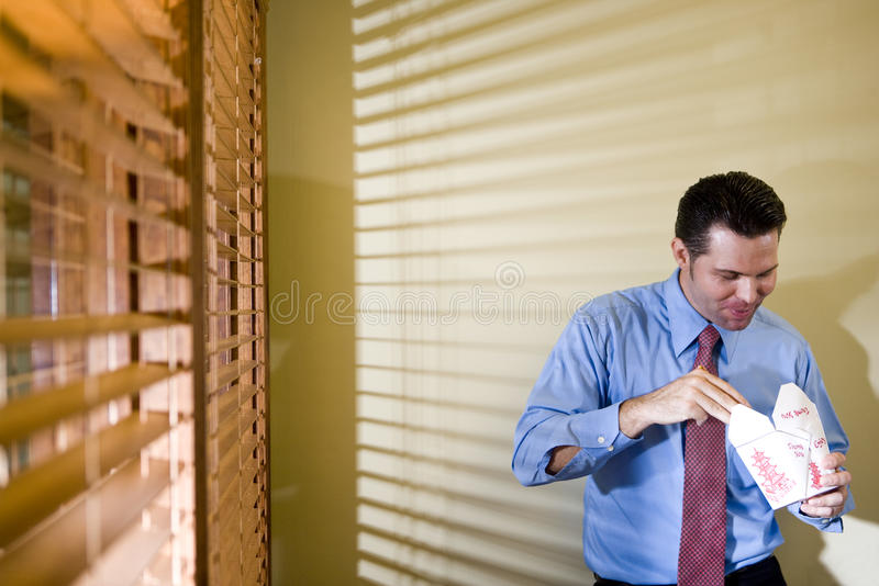 Male office worker eating Chinese takeout. In boardroom stock images
