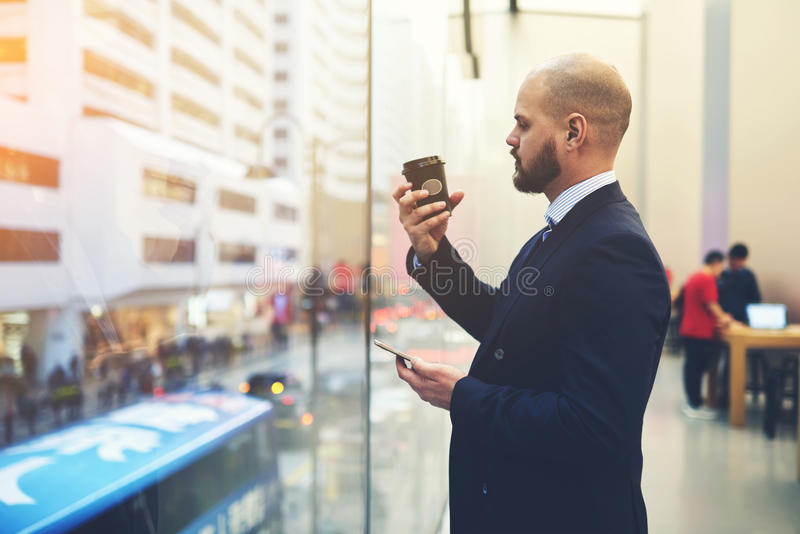 Male office worker use cell telephone. Handsome man dressed in luxury suit is holding mobile phone in hand and watching on brand of take away cup coffee with royalty free stock images