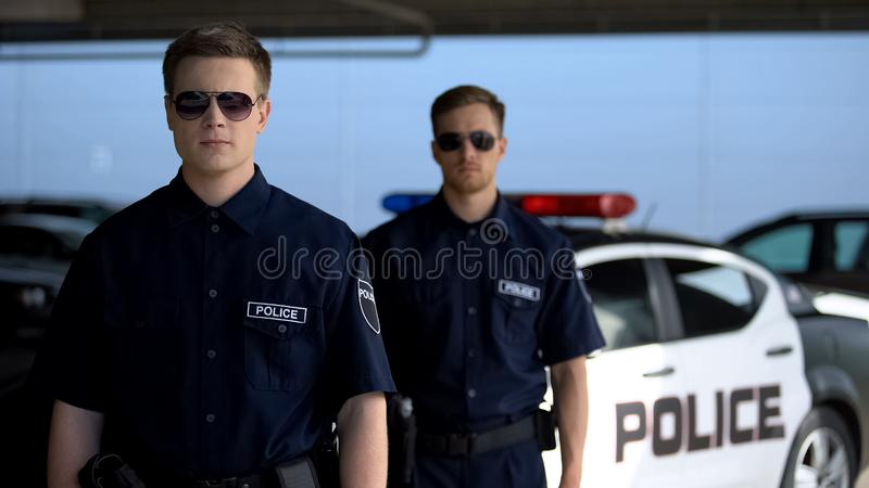 Male officers in sunglasses standing against squad car, ready for patrolling. Stock photo stock image