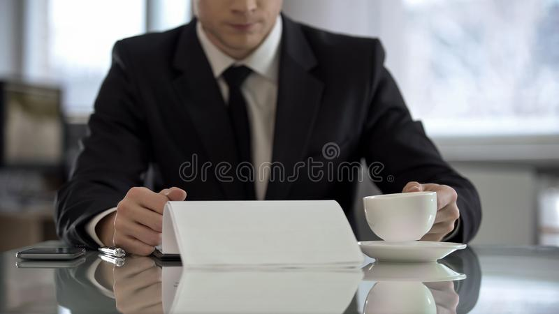 Male official drinking coffee in office and reading text of contract for signing. Stock photo stock photos