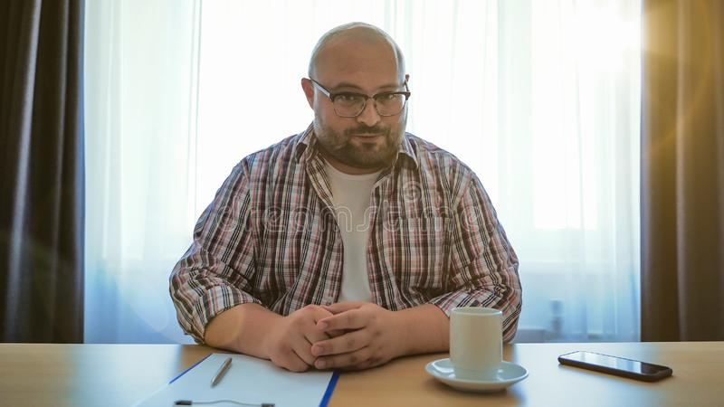 Male online teacher speaks on laptop webcam, fat man in glasses making videocall or webinar or job interview or talks. With far friend via internet stock photo