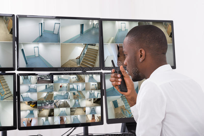 Male Operator Talking On Walkie-Talkie. While Looking At CCTV Footage stock photography