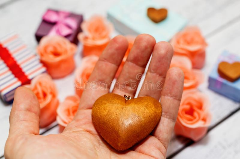Male outstretched hand with wooden vintage heart stock photo