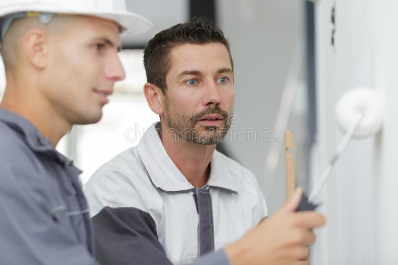 Male painter and apprentice stock photography