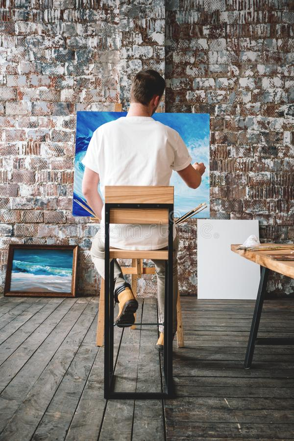 Male painter sits on chair in front canvas and drawing picture in studio. Art class and workshop. Artist painting process. Hobby. Vertical royalty free stock photo