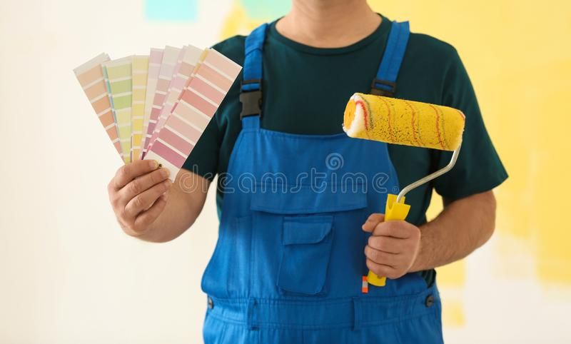 Male painter in uniform with color palette samples and roller brush on colorful background royalty free stock photography