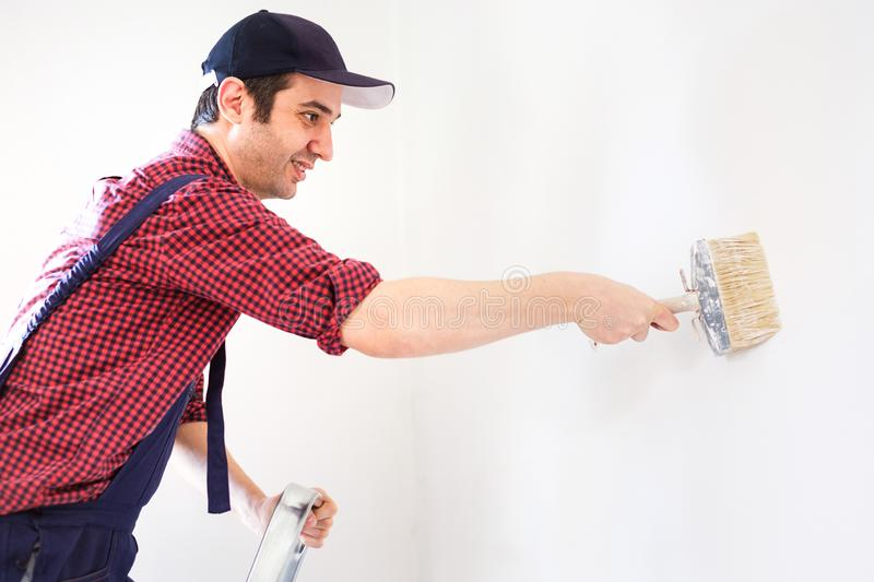 Male painting his white home walls with brush on stepladder stock photography