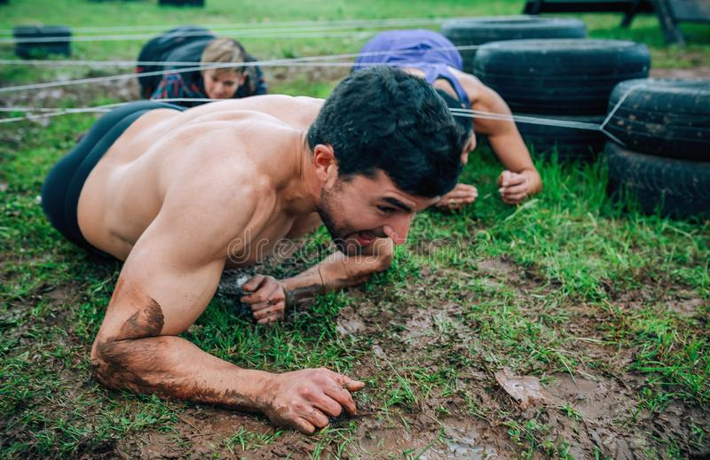 Male participant in an obstacle course crawling. Under electrified cables with partners in background royalty free stock image